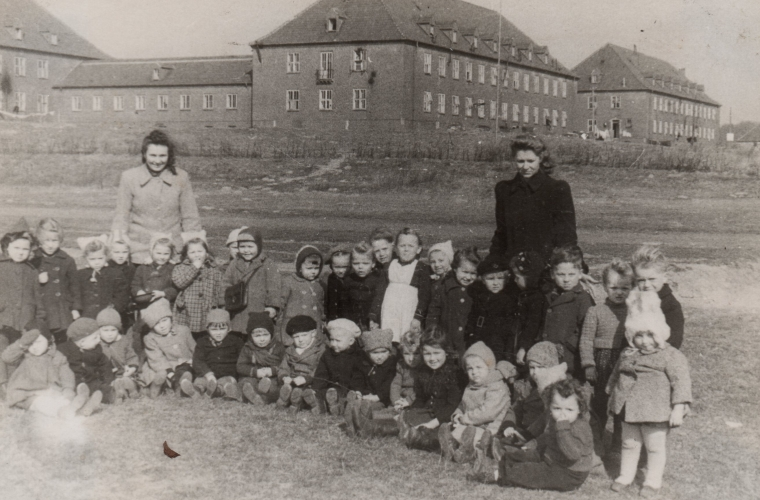 A group of young  children in the foreground, a few hundred metres from the Flensburg DP buildings