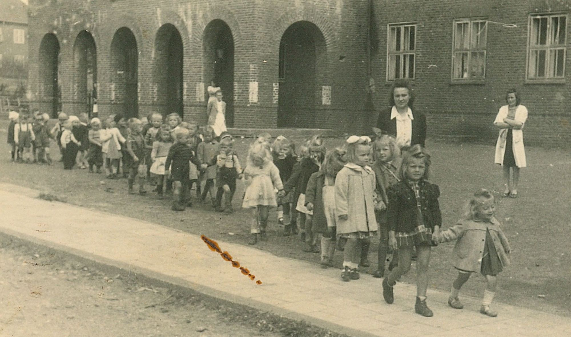 A crocodile of  children walking from left to right along a path in front of the stark Flensburg DP buildings