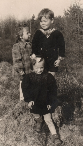 Three children  perched on a rock with pine trees around them. Halina is looking up at the boy, and another little girl is sitting in front  of them, on the rock