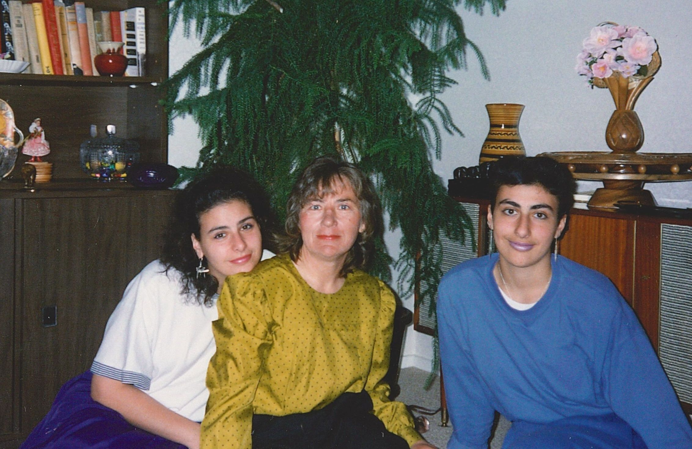 A coloured  photograph with Halina and her daughters sitting on the floor in front of a Christmas tree. Halina is in the middle. One  daughter has her chin on Halina's shoulder
