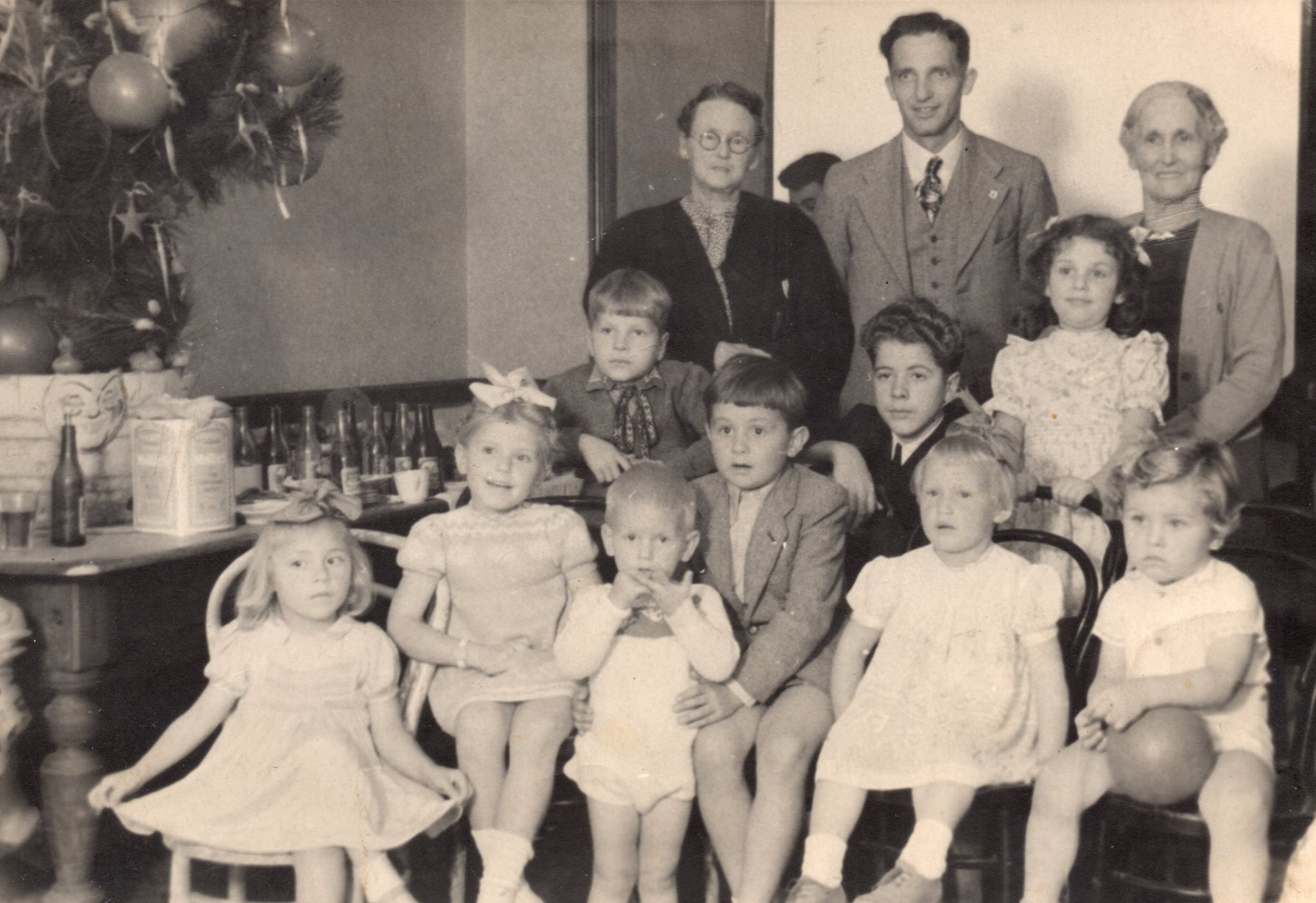 A group of  refugees at a Christmas function, nine childen, five sitting in the front on chairs, and three adults standing behind them.  Part of a Christmas tree is on a table to the left.