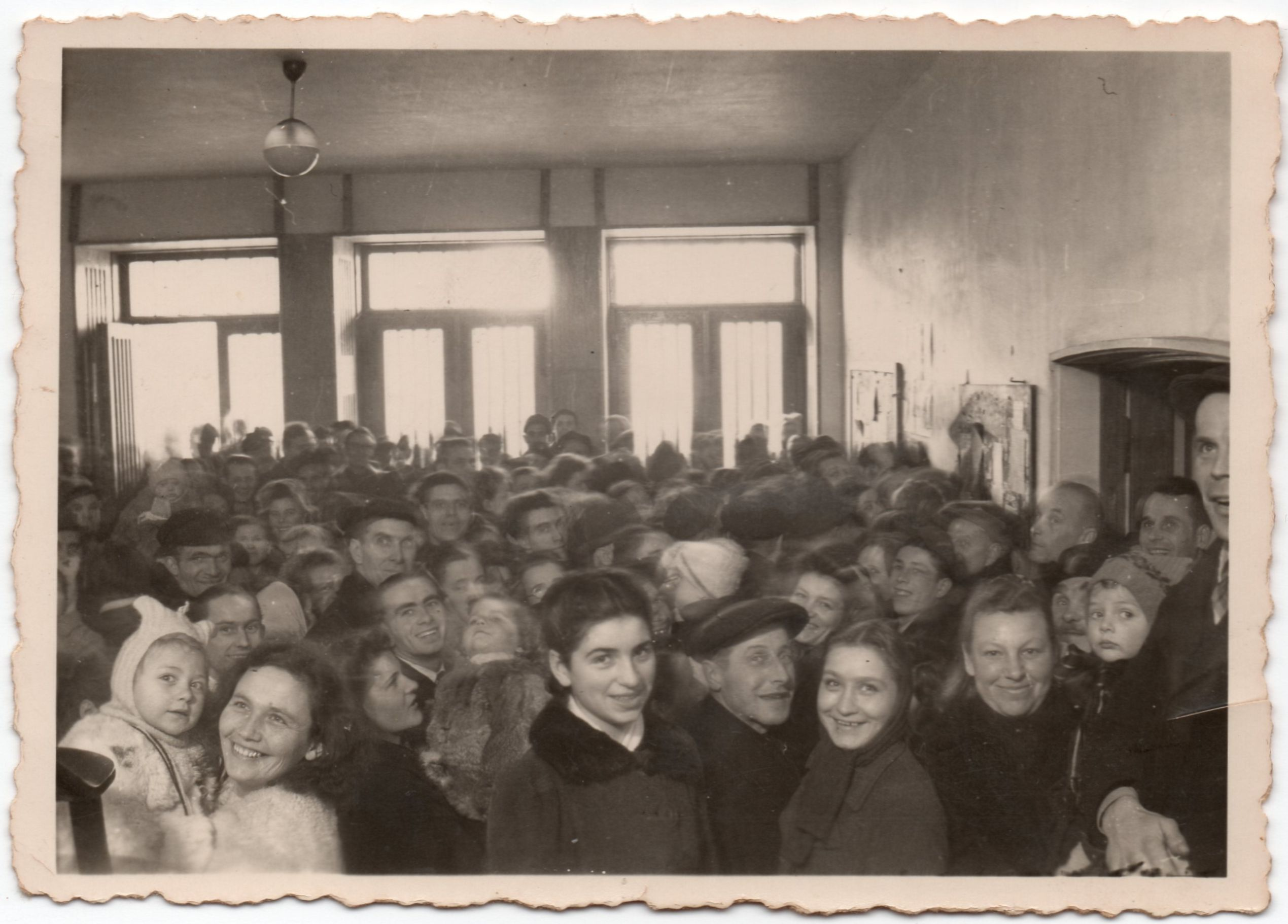 An  immigration hall packed with new immigrants. People fill the bottom of the photograph. The top half shows a plain room with  three large windows at the back.