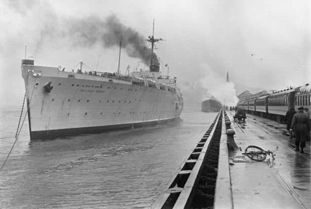 The ship alongside  the wharf, which has a train waiting. The ship, and one behind, are spouting smoke. A man is walking front right away from  the camera