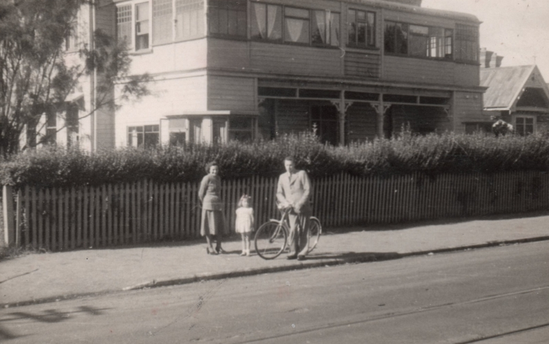 The Kuźmiuks are  standing on the pavement outside the hotel, which looks like a large house, and which borders the pavement with a low fence  and a hedge taller than Pawel, who is astride a bicycle.