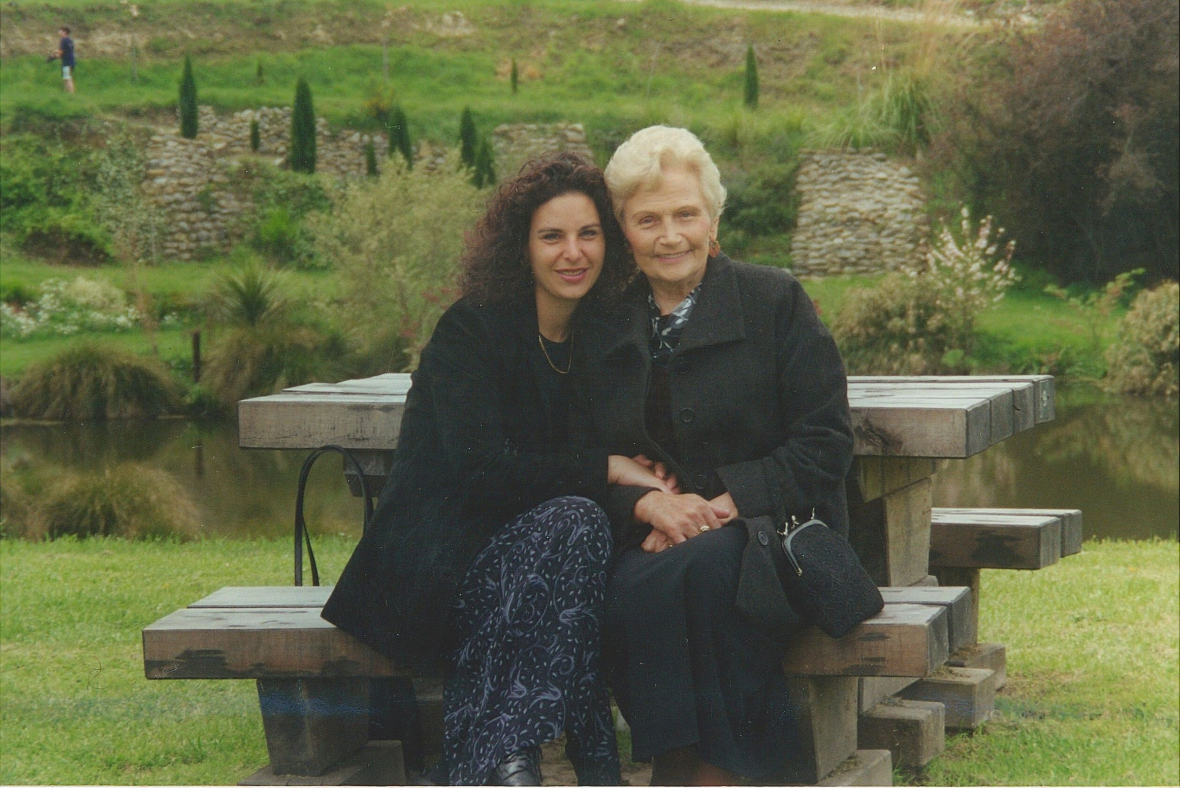 Irena Kuźmiuk sitting with her granddaughter at a picnic table in a Christchurch park.