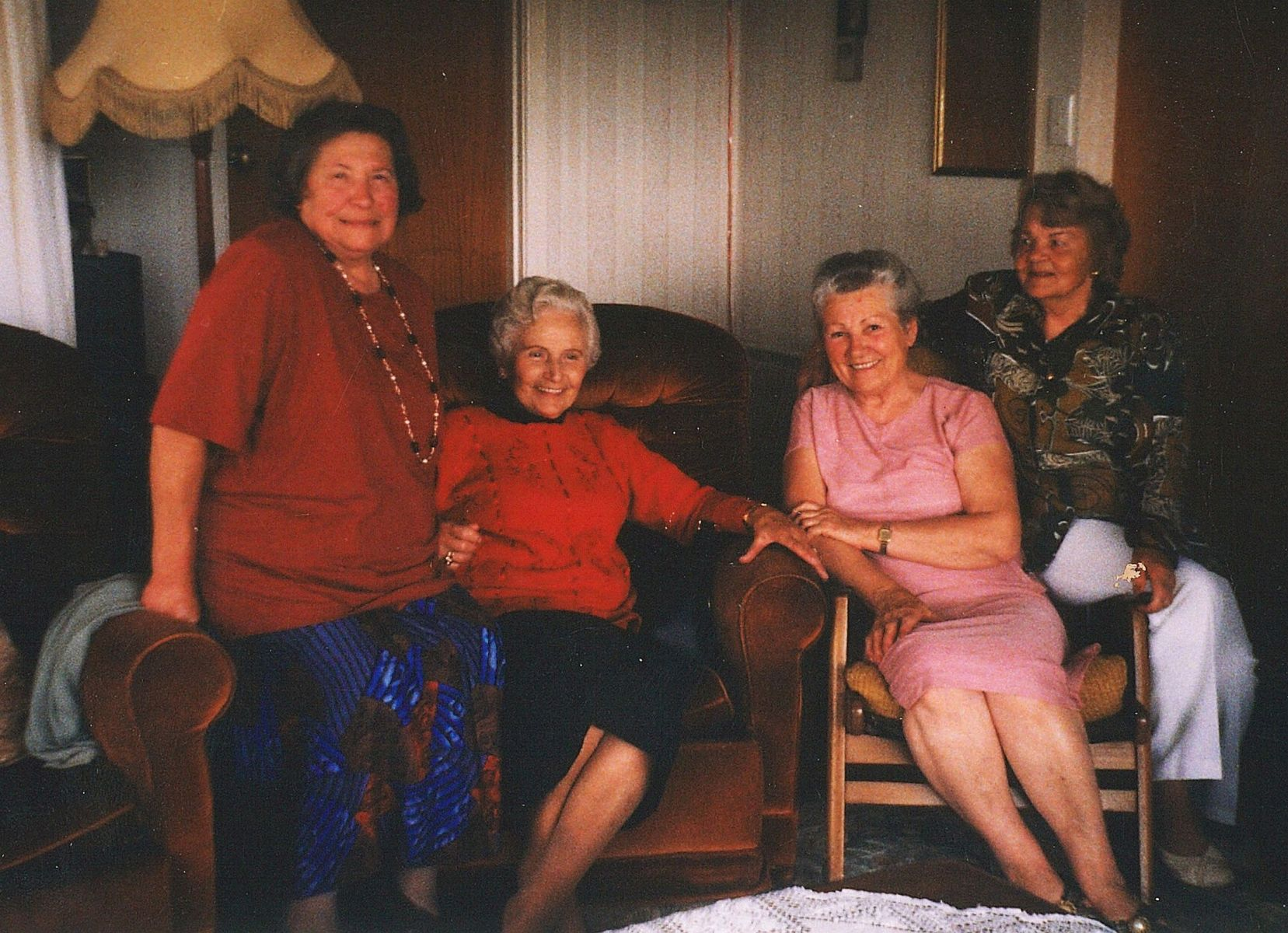 Four  middle-aged women in a lounge, the middle two sitting on chairs and the outer two perched on the armrests. All are smiling.