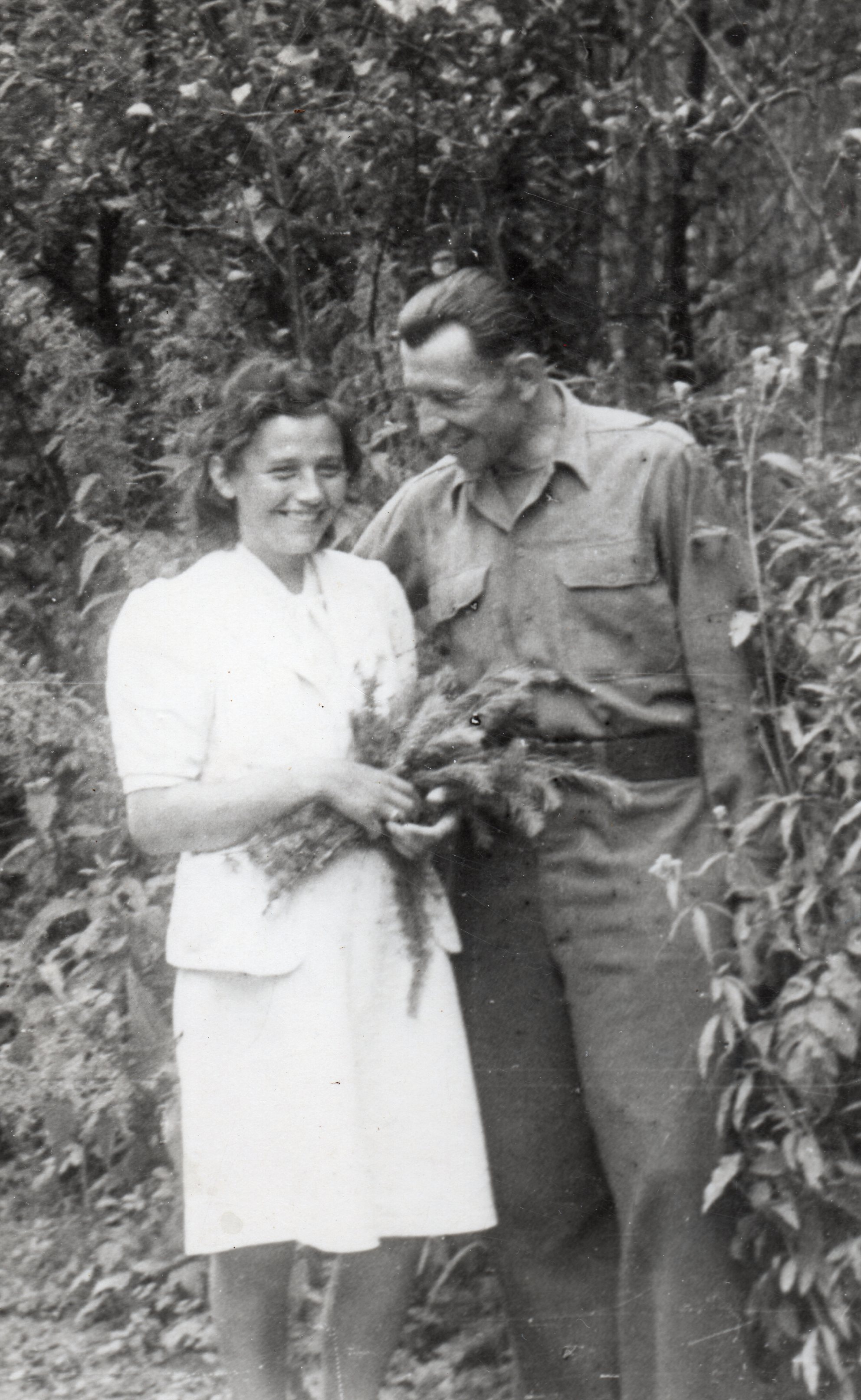 A black  and white photo of Paweł in army fatigues, and Irena in a white suit. She has some greenery in her hands. Both are smiling  widely and Paweł is looking down at Irena.