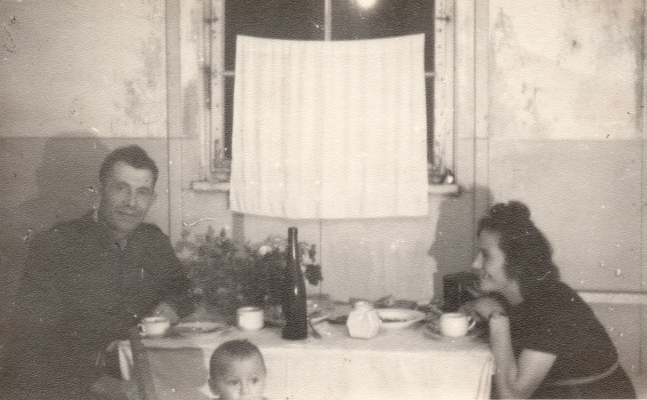 Paweł , in an army  uniform, and Irena sit on either side of a laid table with a white cloth. Paweł  is looking at the camera and Irena is  smiling at him. Halina's head just visible at the bottom.