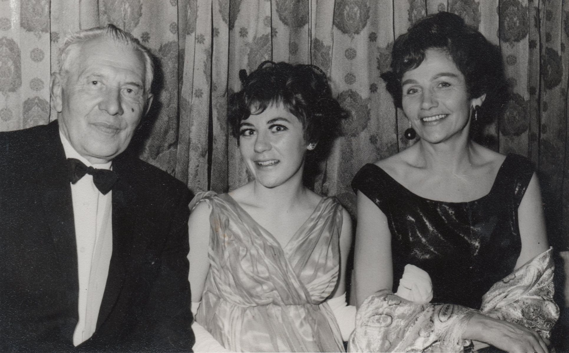 A black and white  photo of the family, Hania in the middle of her parents, all dressed in formal attire.
