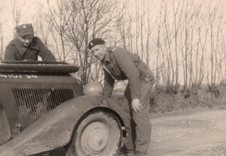 Paweł  Kuźmiuk  looks up and smiles as he leans over the open engine of an army vehicle. Another soldier is head down over the engine. Flat  fields, and leafless thin trees line the road behind him.