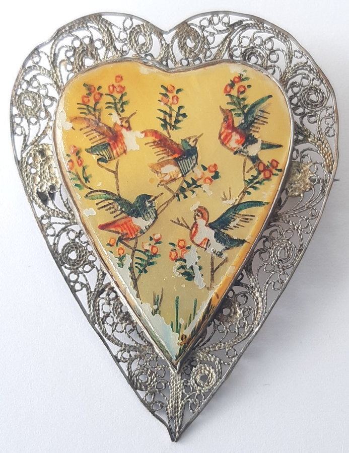 A heart-shaped brooch,  filigree metalwork on the outside and five painted birds with flowers on the inside, slightly tarnished now but still  beautiful.