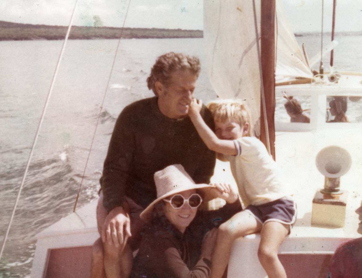 Ken sitting in front of the  mast, Zofia in sunhat and glasses, lower down. The little boy had his arms around dad's shoulder.
