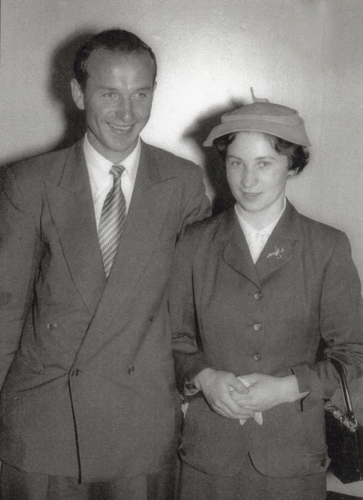 A black and white  photograph of the two in mid-toned suits, Jan smiling to someone on the right of the phnotographer. Irena, wears a hat, holds  gloves and with a handbag on her arm, is looking demurely at the potographer.