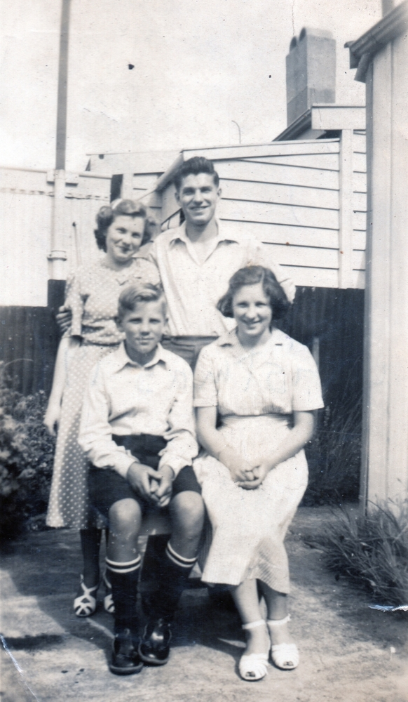 A happy photograph of the  siblings, two sitting, two standing in the yard. Czesław has his arm around Zofia, who is leaning her head towards him.  Zdzisław is in school uniform.