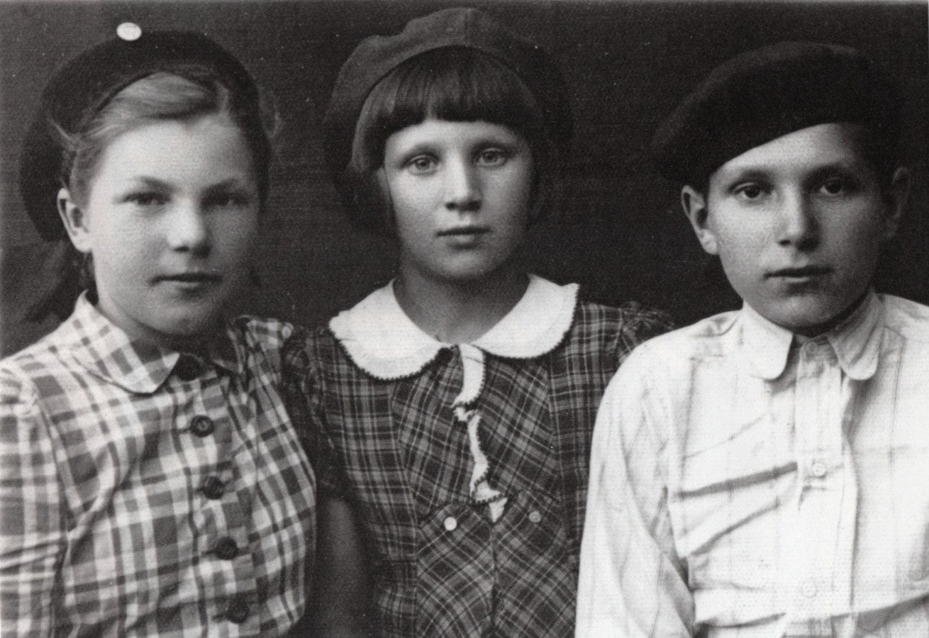 A black and white  photograph of the three neatly dressed siblings. Czesław is in a light shirt buttoned to the neck, and the girls are wearing  checked dresses; Zofia's buttoned to the collar and Irena's with a prettier, white collar. All have serious expressions.