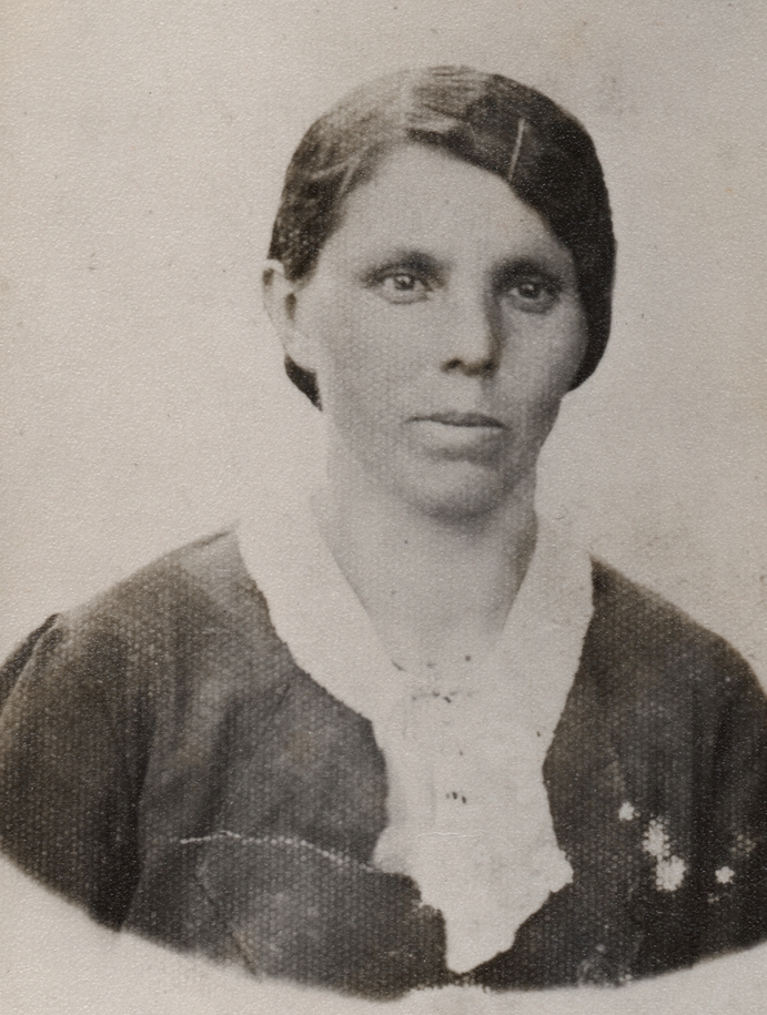A black and white  head and shoulders shot of Leokadia, with her hair brushed back, a hairgrip keeping it away from her eyes, serious, and  wearing a dark dress and wite collar