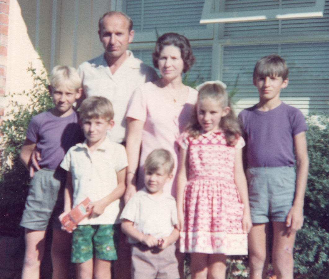 A coloured but  slightly blurry summer photograph of the family outside a house. The parents are at the back, the children in front of them.  the two boys on either side are wearing matching purple tee-shirts and grey shorts.