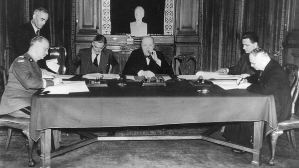 A black and white  shot of five seated men at a table. There is an unidentified man standing on Sikorski's left, and another unidentified man  sitting on the other side of the camera to Maisky. All ezcept Churchill are looking down. Churchill is looking directly at  the camera.