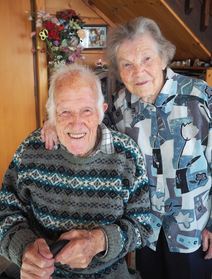 An inside, happy  photograph of Zofia and Ken Derrick. Ken is sitting and Zofia is standing behind him with her hand on is shoulder.