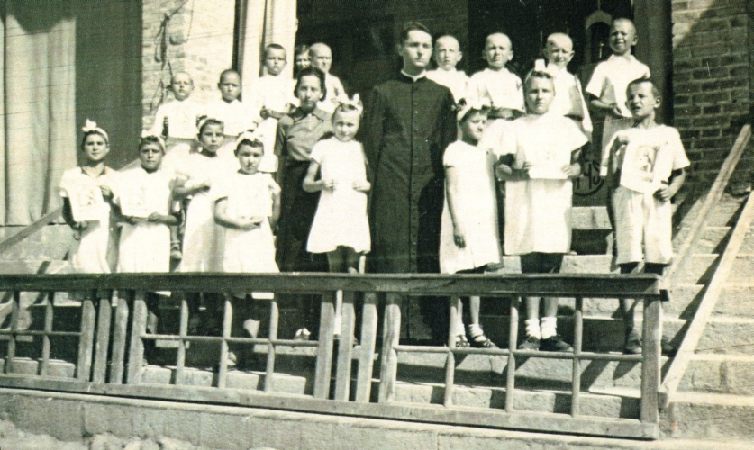 Group of  children outside a church with priest
