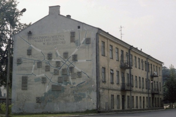 Message,  map and raised site markers, painted in mostly dull grey shades on the side of an apartment block in Białystok 1980s
