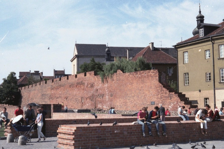 People sitting on  the broken wall in Warsaw's Old Town, on a sunny day