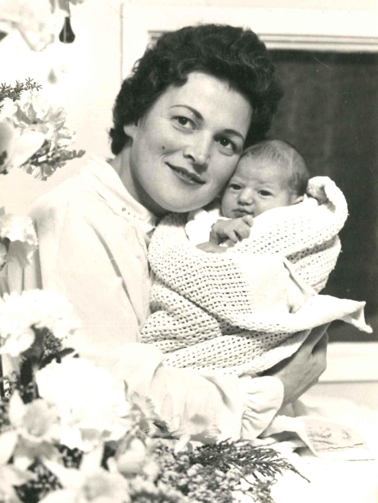 Black and white  hospital-bed photograph of Marysia Jaskiewicz, dressed in a light night-jacket, smiling and looking up to the left, and  holding her new-born daughter, wrapped in a light blanket, and with the usual new-born squished look.