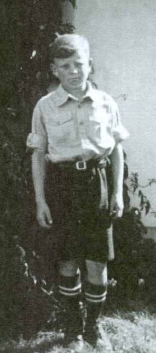 Joe Jagiełło aged  about 12, standing alone, serious expression