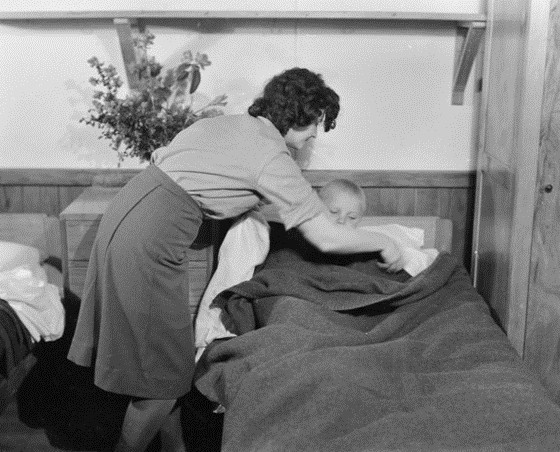 Young Polish boy  being tucked into bed by unidentified woman, in skirt and shirt, possibly WAAF uniform