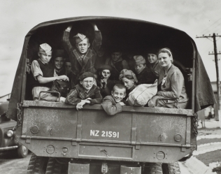 Polish boys with woman  caregiver looking from the back of an army truck