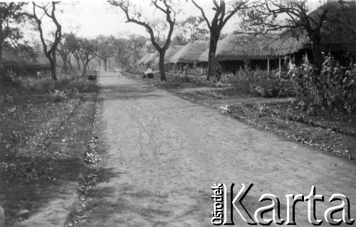 1945 black and  white pic of a street in one of the Masindi camps, showing dirt road, thatched houses and trees