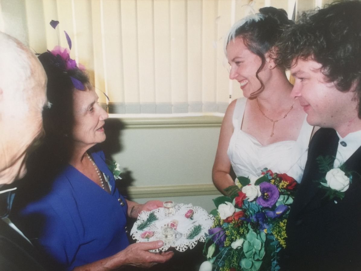 Joanna greets  her daughter and new son-in-law with a dainty tray covered with a crochet cloth and decorated with greenery and rosebuds. The  two shot glasses are visible. Tadeusz is at Joanna's side, back to the camera.