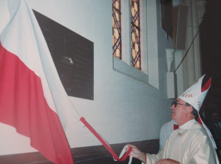 The bishop pulling away a  Polish flag from the plaque