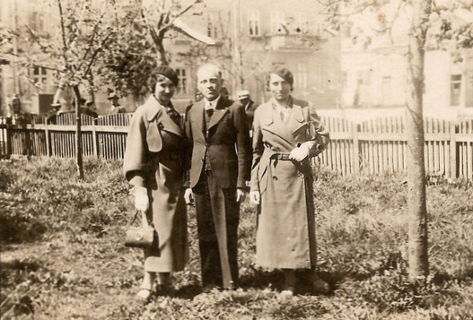 Józef  Zając with Bronisława and Maria on either side, standing in a garden, fence at background and faint view of nearby houses