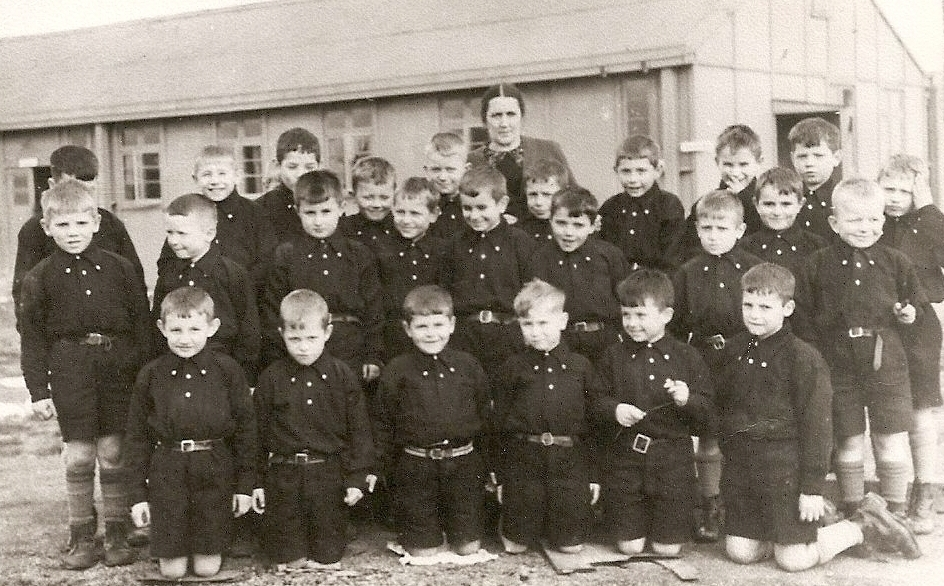 Three  rows of young boys dressed in dark shirts and shorts with Mrs Petrus at the back.
