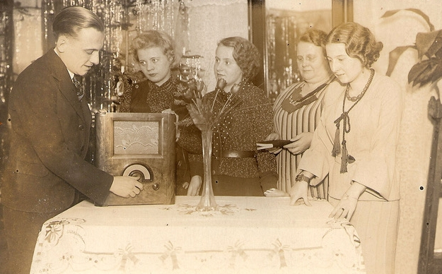 Josef mansplaining  a wireless to four elegantly dressed women around a table with a white, embroidered tablecloth and a tall glass vase with  roses. Josef has his hand on the wireless knob, as the two youngest look adoringly at him, an older woman looks down at a  book and the fourth looks at the table.