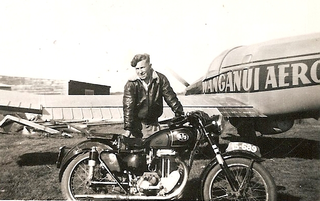 Kazik  behind his motorbike, in leather jacket, and part of an aeroplane with Wanganui Aero written on the side.