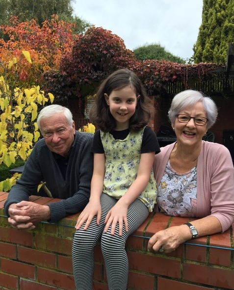 Kazik, Jan and  their granddaughter, Lucy, in the garden, Lucy sitting on a wall.