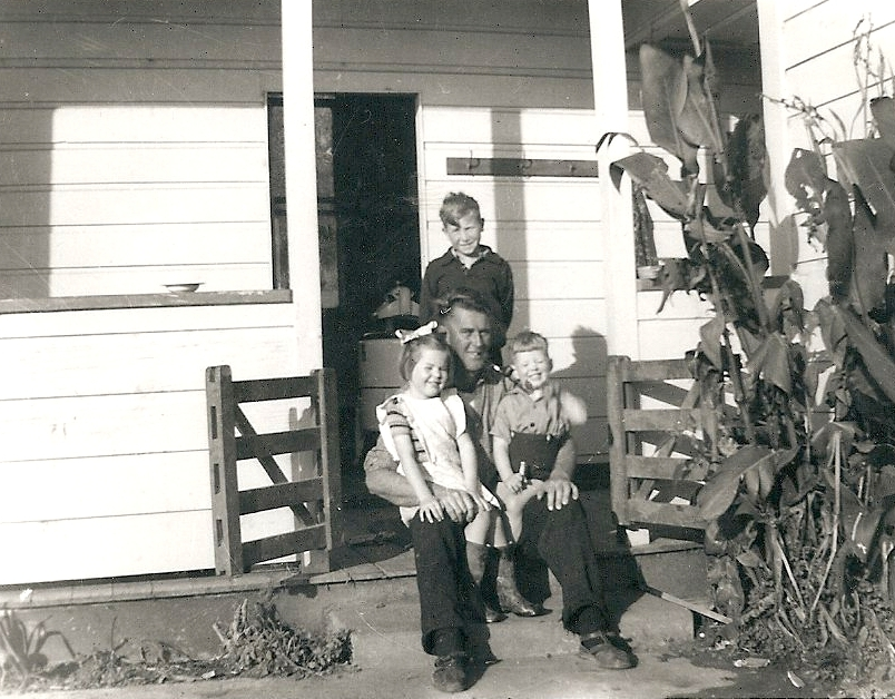 Outside a white  weatherboard door, on a porch, Kazik stands behind John Campbell, who is sitting on the step with his two oldest children on  His knees.