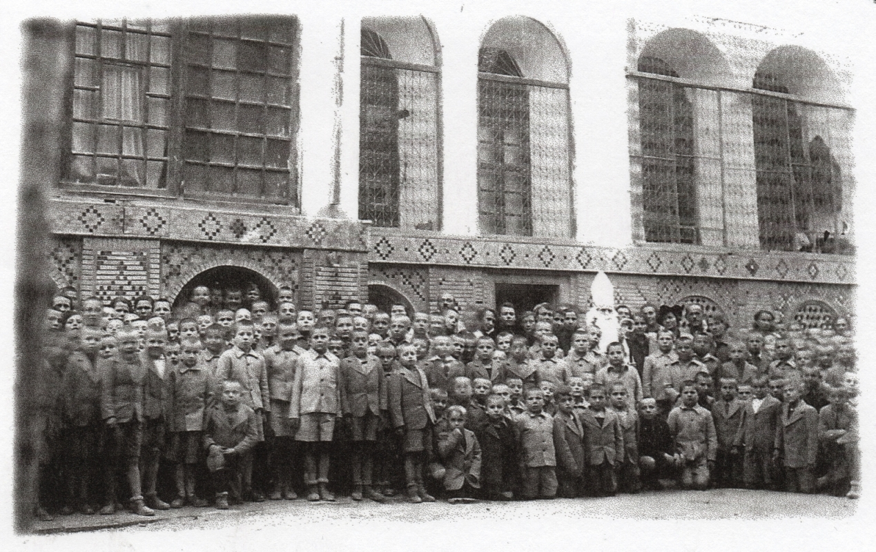 A far more sombre  black and white group photograph of the boys, wearing long-sleeved jackets, in front of their building, ornately decorated.  Above them are the arch-shaped dormitory windows