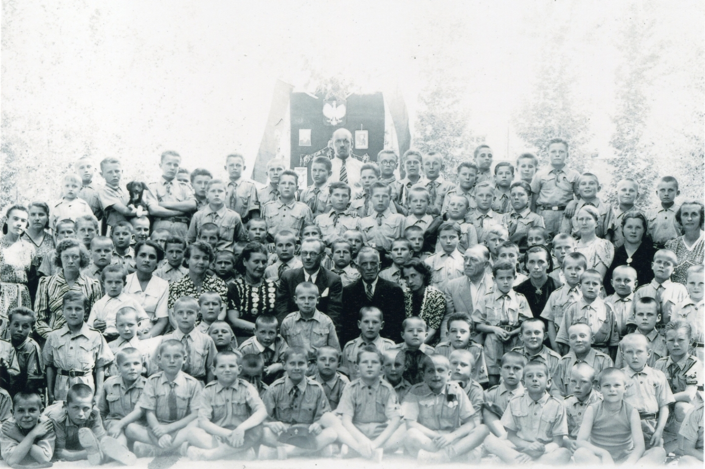 A black and white  group photograph of at least 60 young boys, wearing mostly military-style uniforms, and caregivers, in front of a banner with  a white eagle. Few smiles, but one boy holding a black dog.