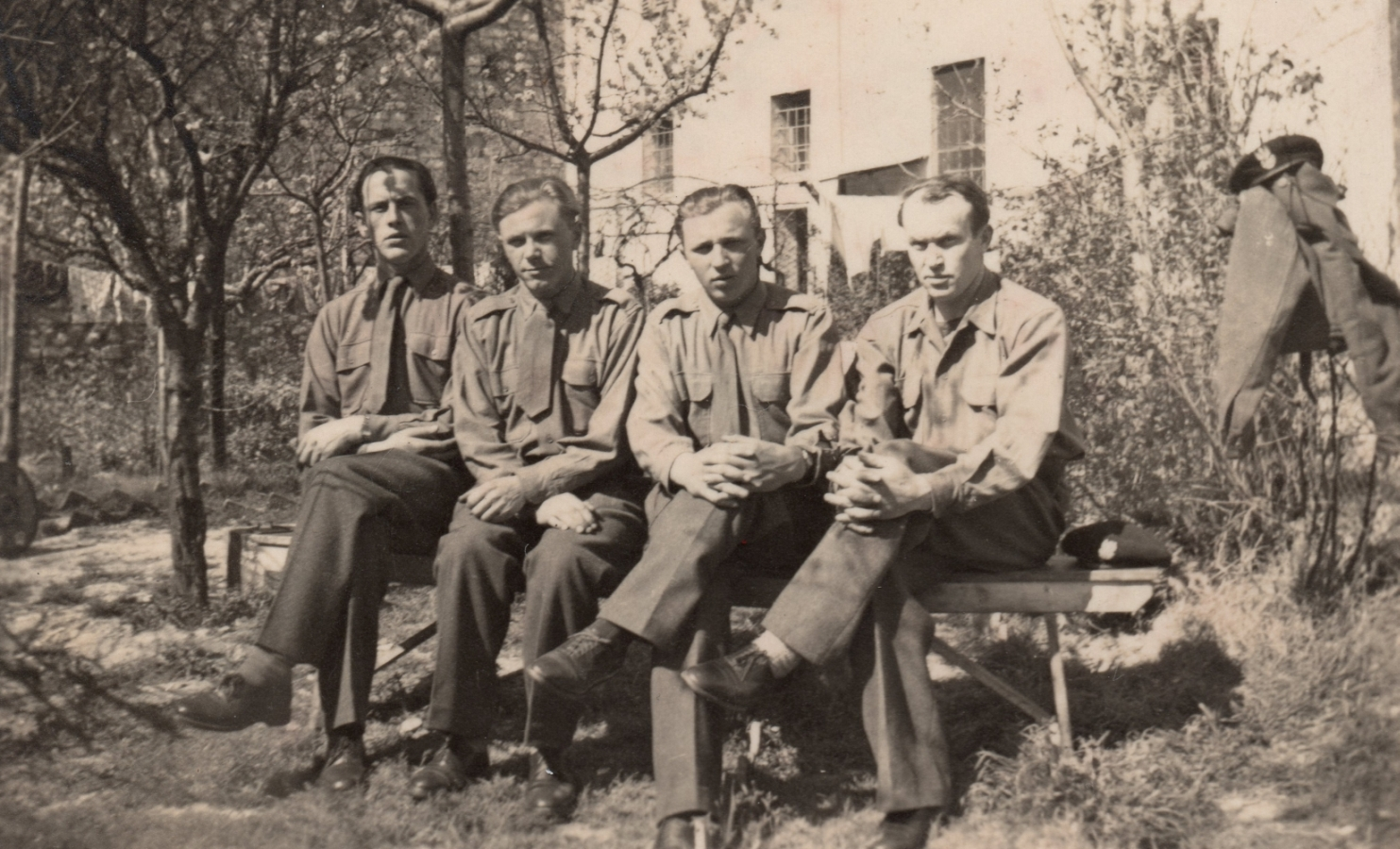 Four soldiers  sitting on a bench under trees in front of a house, in shirtsleeves, no caps, one cap next to the men on the bench, another  placed on a jacket hung over a wire fence.