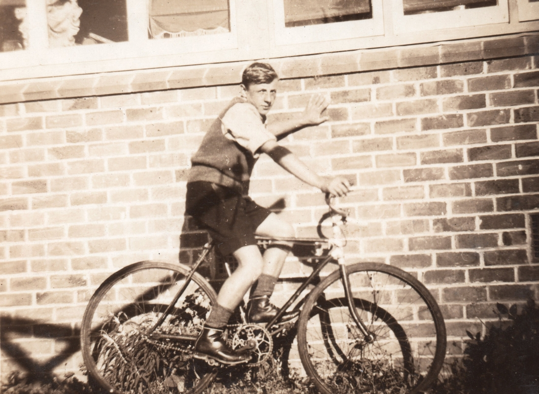 Black and  white photograph of Tomasz, about 15, on his bike and leaning against the brick wall of a house.