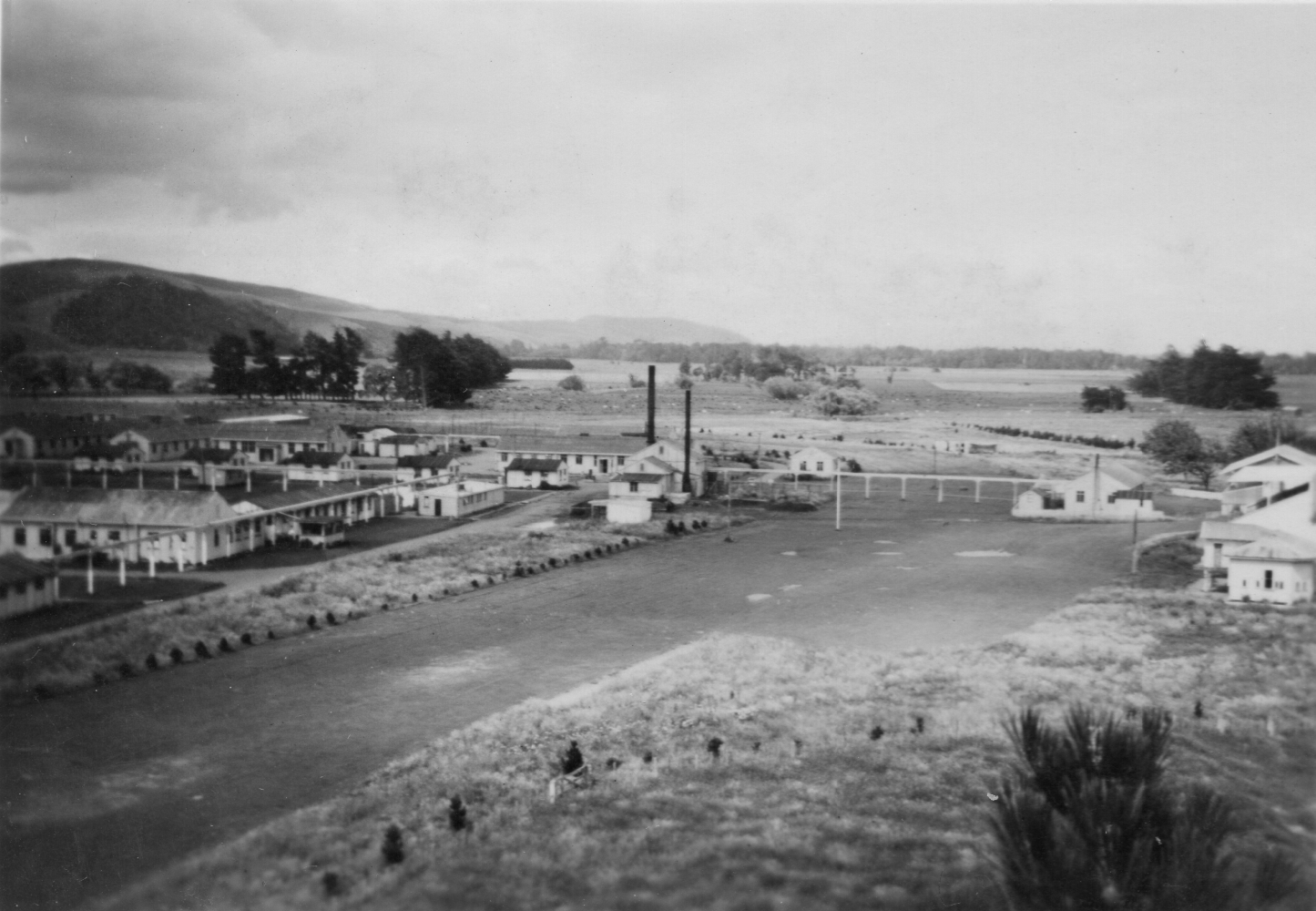 First of seven  black and white photographs of the Pahiatua camp. This one shows the camp on both sides of the old racetrack, pre-fabricated  buildings and hills in the background.