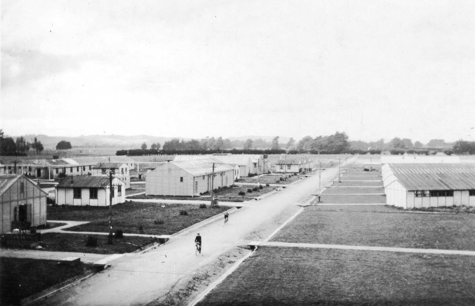 The main street  of the camp, with two boys on thier bikes. Photograph shows how isolated the camp was.