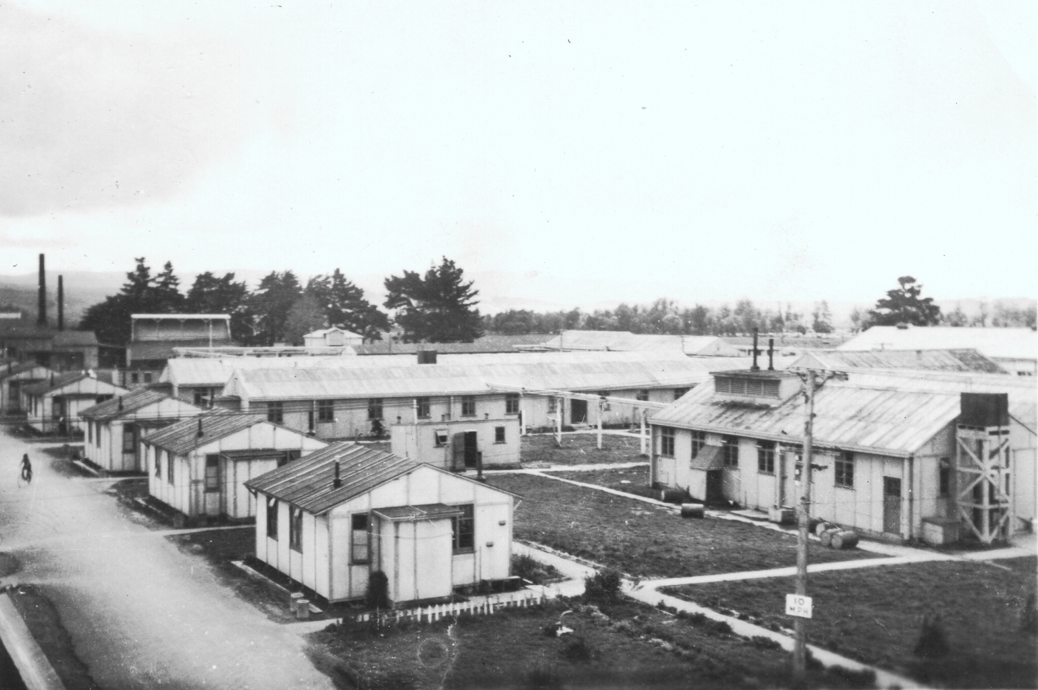 Closer  shot of the teachers' quarters. Several small prefabricated buildings with their vertical joints clearly visible, sitting  between a road and patches of lawn.