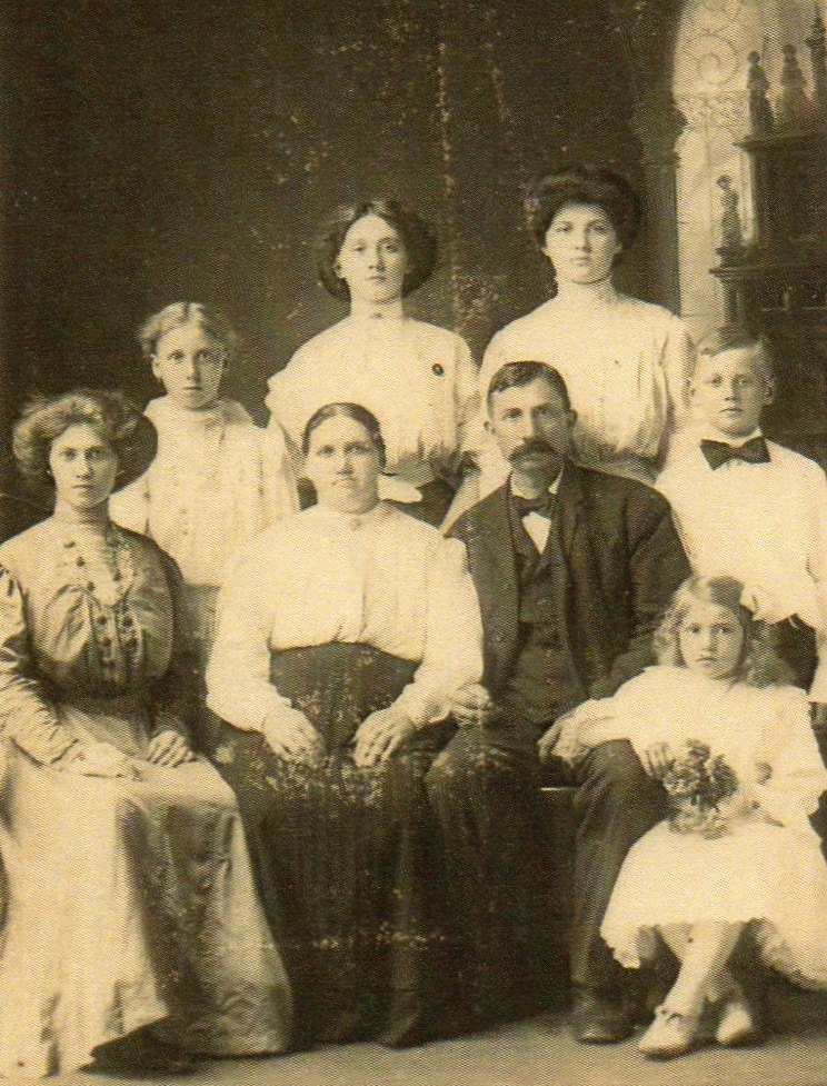 A  blurry studio photo of Clara, her husband and their five daughters and a son.