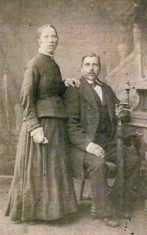 A blurry  studio photo of Franz, seated, his hand leaning on a closed umbrella and Pauline, standing with her hand on his shoulder.