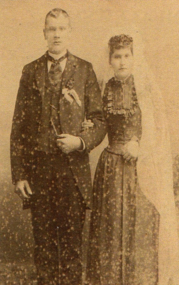 A  blurry studio photo of Johann and Augustine standing in dark formal attire. Augustine has a long white veil.