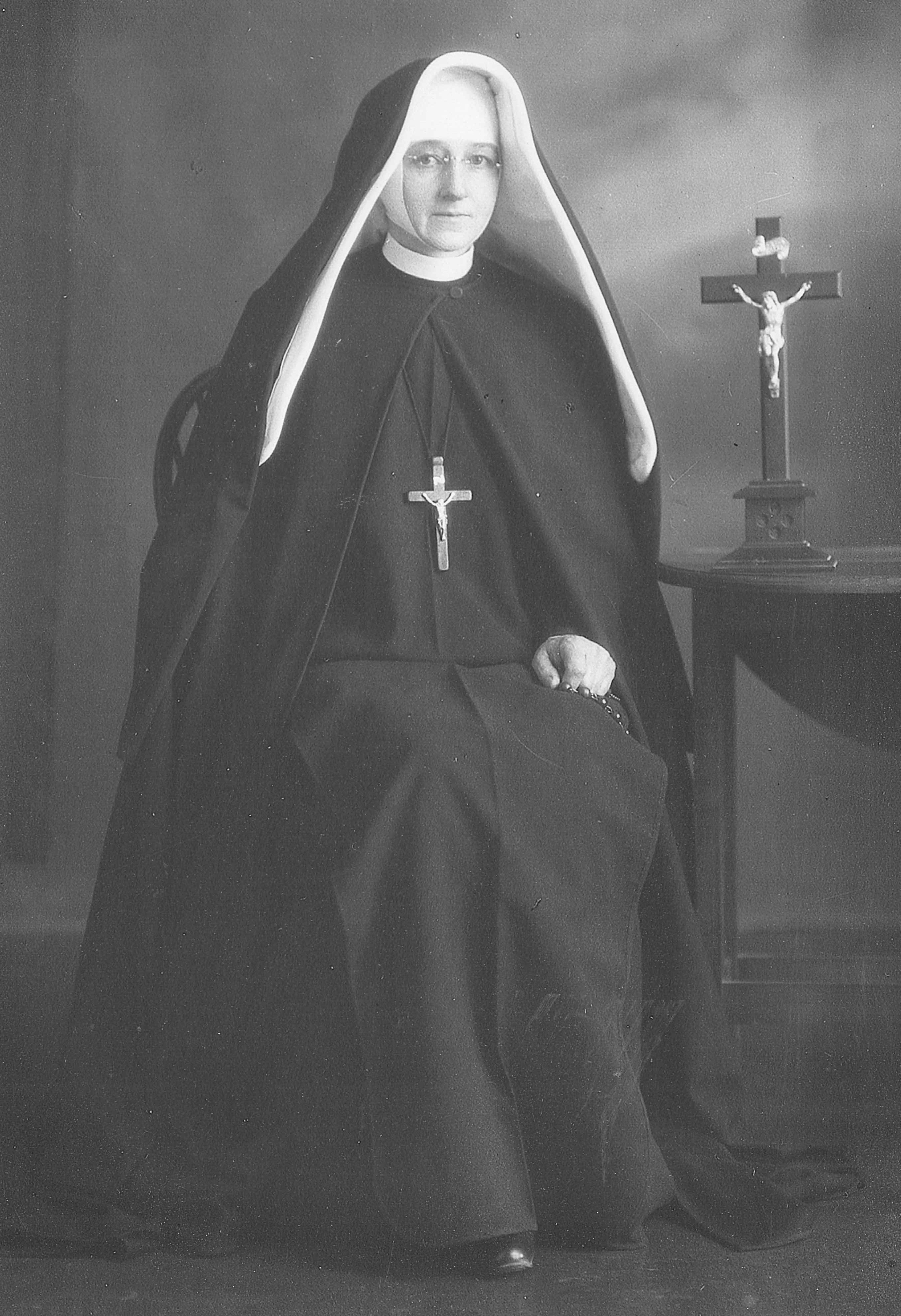 Black  and white photograph of Sr Mary Kostka in her habit, sitting next to a table with a crucifix on it, and holding her rosary.